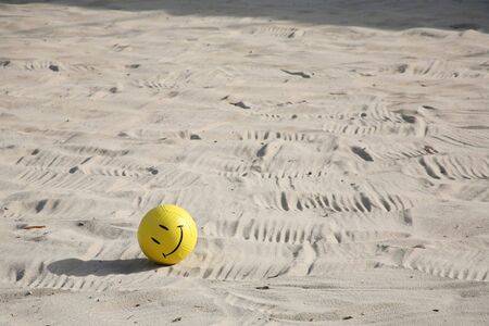 Smiley face on a volleyball on the beach sand photo