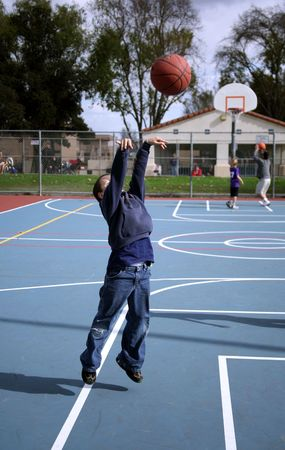 Young boy airborne while shooting a basketball