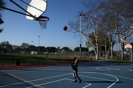 outside shooting: Young girl making a hook shot while practicing basketball