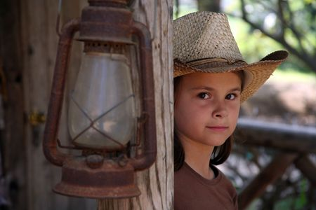 looking around: Young cowgirl looking around a wooden post