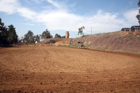 dirt track: Horse arena with a tractor smoothing it and a rock wall in the background Stock Photo