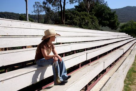 bleachers: Young cowgirl sitting on empty bleachers waiting for the horse show to begin
