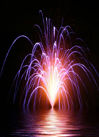 Colorful and beautiful display of fireworks over water photo