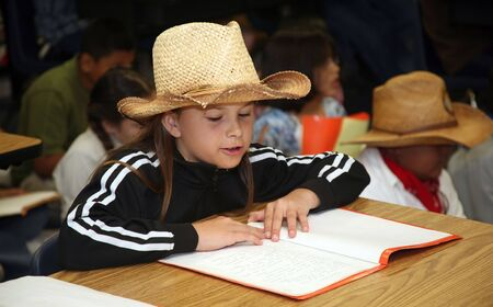 School girl wearing a cowboy hat and singing Clementine photo