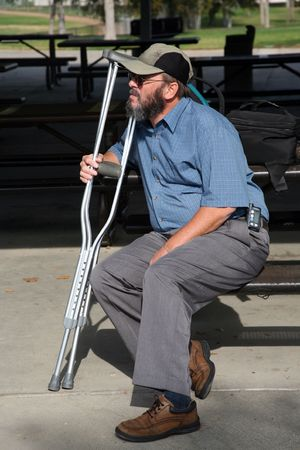 Older gentleman resting on a park bench while holding his crutches and contemplating his accident