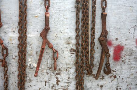 Abstract chain hanging over a weathered piece of wood or fence photo