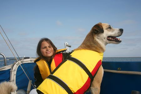 dog teeth: Akita and Australian shepard mixed breed dog and girl sailing across the water