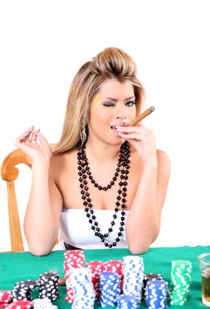 gambler: Beautiful woman smoking a cigar while playing poker Stock Photo
