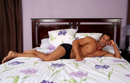Sexy hot male model lying on a bed Stock Photo - 1477012