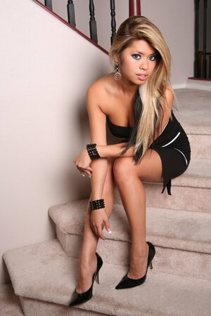 Sexy hot brunette woman sitting on the stairs photo