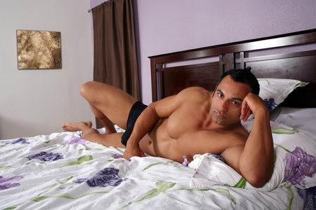 Sexy hot male model lying on a bed Stock Photo - 1528211
