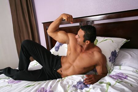 Sexy hot male model admiring his muscles Stock Photo