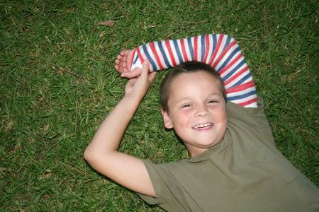 fractura: Chico joven sentar sobre la hierba con un yeso en su brazo