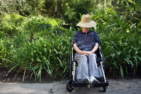 Handicapped senior woman sitting in a wheelchair photo