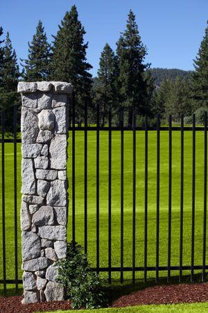 Lush golf course behind a wrought iron fence Banco de Imagens