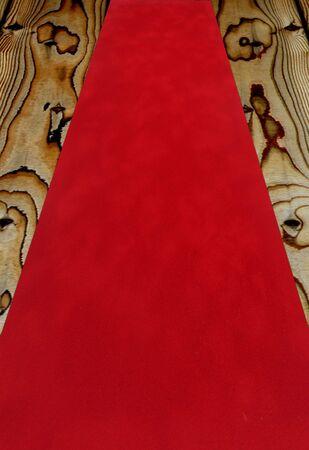 red carpet background: Red velvet carpet fabric over a wooden floor