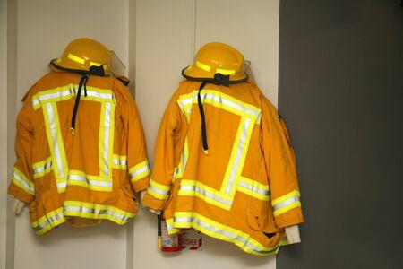 estacion de bomberos: Chaquetas y cascos del bombero que cuelgan en el parque de bomberos