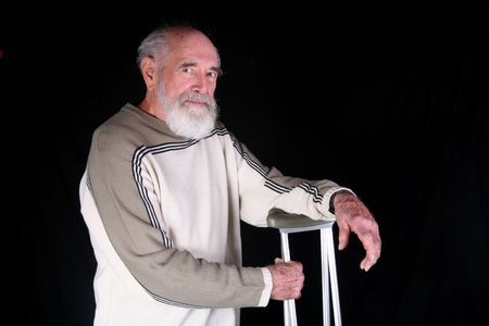 Man resting on his crutches isolated on black background photo