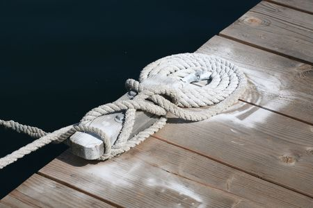 cleat: Boat rope secured to cleat on the dock Stock Photo