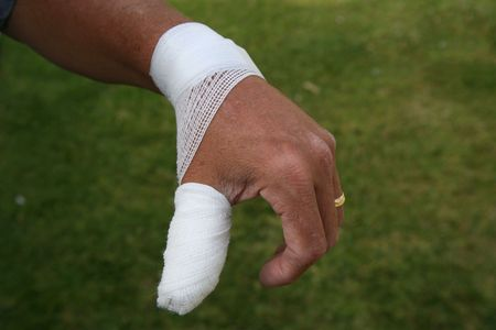 Hurt thumb with surgical dressing on the hand of an older man wearing a wedding ring