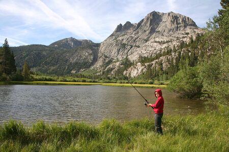 Young fisherman enjoying nature in the High Sierras of California photo