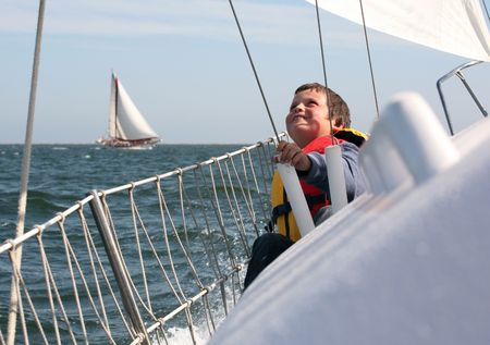 Young boy with ocean spray on him showing his joy of sailing