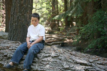 Jonge jongen die verschijnt triest te zitten op dit log in het bos