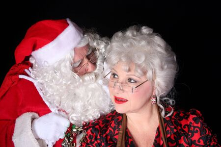 Santa Clause whispering into the ear of his wife