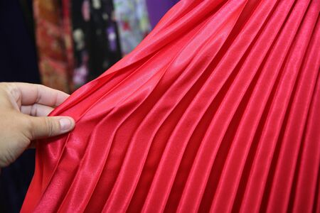 pleated: Woman shopping for clothing and inspecting a red pleated skirt or dress