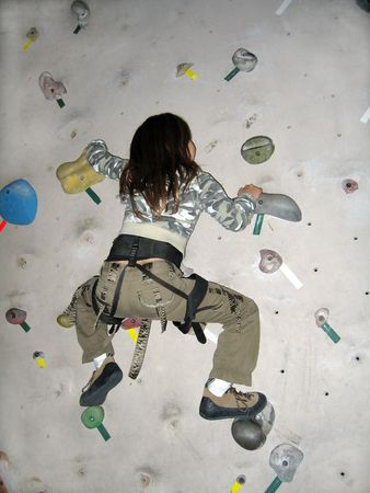 gripping hair: Young girl wearing camouflage climbing an artificial rock wall Stock Photo