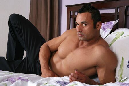 Sexy male model lying on a bed in a bedroom Stock Photo - 3414150