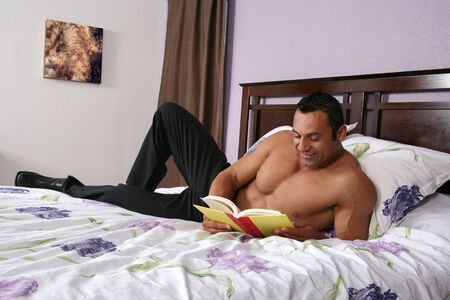 bare chest: Sexy male model reading something funny in a book
