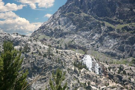 sierras: Waterfall coming off a mountain in the High Sierras California with blue cloudy sky