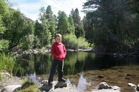 sierras: Young boy enjoying nature next to a stream in the High Sierras California Stock Photo