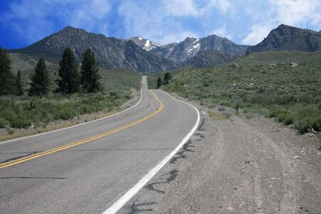 Road leading to snow spotted mountains with blue sky photo