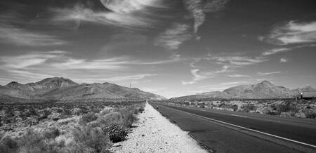 Black and white road with a semi truck heading to the horizon photo
