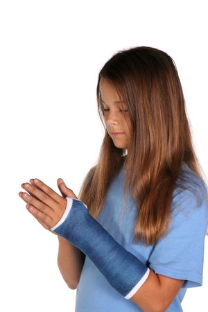 broken wrist: Young girl with a cast praying isolated on white background