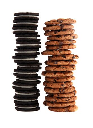 Stack of chocolate chip cookies and cream-filled sandwich cookies isolated on white background Foto de archivo