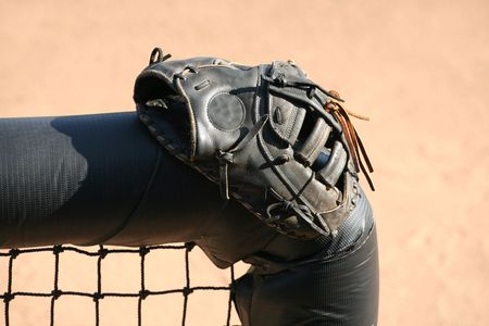 baseball dugout: Baseball or softball glove resting on a dugout fence