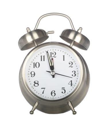 Isolated old fashioned alarm clock set for midnight on a holiday such as New Years Eve on white background photo