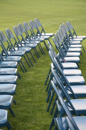 Rows of blue chairs on green grass background