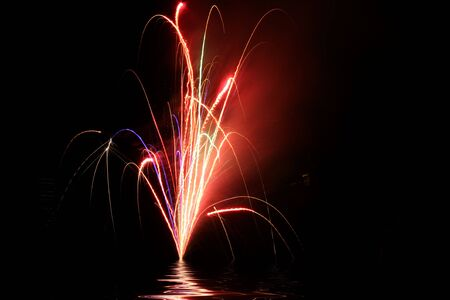 Patriotic colored fireworks background on black night sky over water Stock Photo