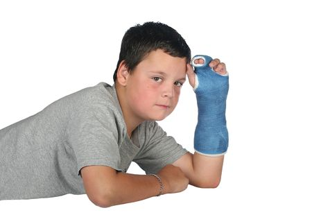 Young boy wearing a cast with a tear coming from his eye due to the pain photo