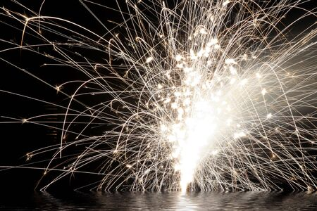 White fireworks display on black sky background with water reflection