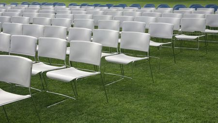 Rows of chairs on green grass background