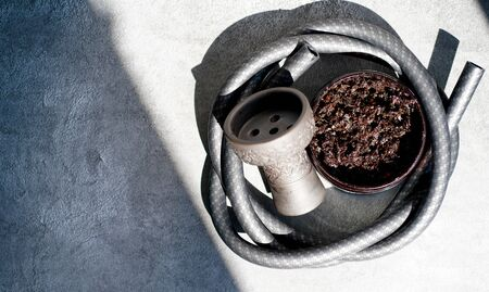 tobacco for hookah, bowl and hose on a gray concrete background. Traditional oriental holidays.