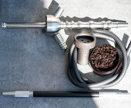 Steel hookah shisha, mouthpiece and clay bowl, hose, tobacco on a gray concrete background