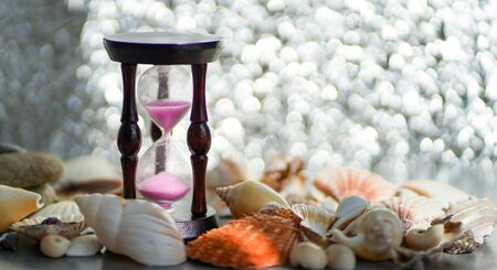 Hourglass and seashells on a silver background. blurred focus. Imagens