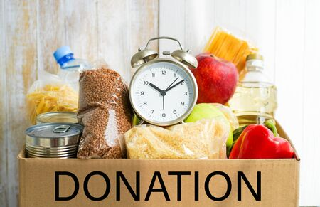 Donation box with various food. Open cardboard box with a clock alarm clock oil, canned goods, cereals and fruits.
