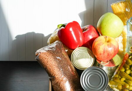 Donation box with various food. Open cardboard box with butter, canned goods